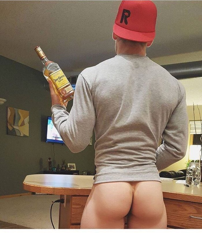 z used bare bum holding whisky bottle